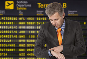 A man checking his watch waiting on transportation for corporate travel